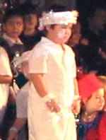 four year old boy on stage, all in white, with white tinsel trimmings