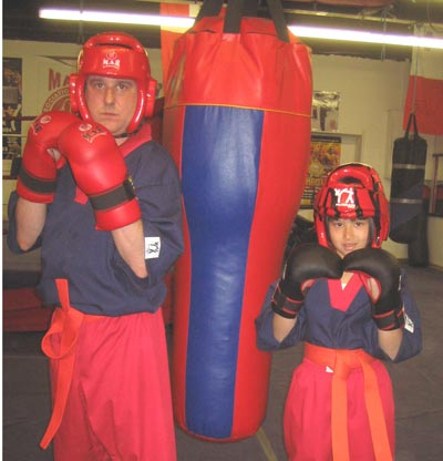 40 year old man, 8 year old girl, with boxing gloves and helmets next to punch bag