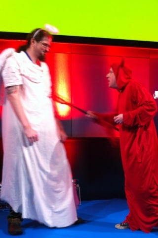 Bruce, dressed as a devil, poking a pitchfork into Chris Mills' stomach, who's dressed as an angel