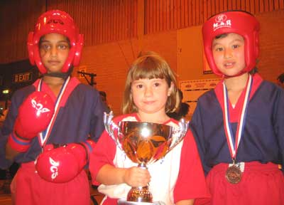 three eight year old girls, one two in karate headguards, the other holding a trophy