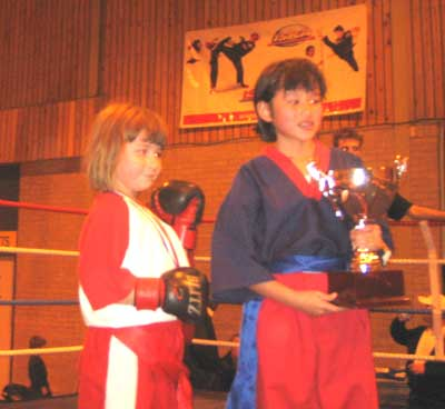 two eight year old girls in a boxing ring, one holding a trophy