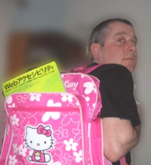 me, wearing pink Hello Kitty backpack, from which protrudes a green  book with Japanese writing on the front